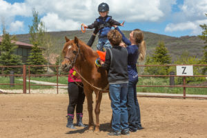 Tulip the NAC horse with participant on her back, assisted by a volunteer and NAC staff member
